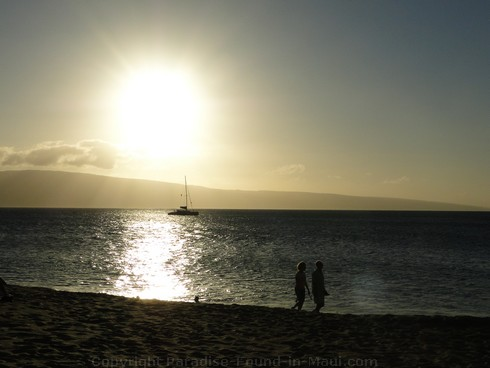 Picture of a couple walking on Kaanapali Beach, Maui at sunset.