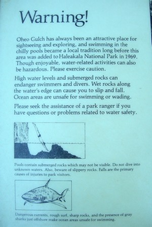 picture of warning sign at Oheo Gulch (Seven Sacred Pools) where stream empties into ocean... warns of sharks and strong currents etc.