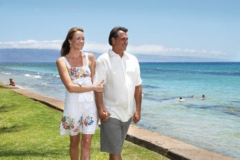 Picture of a couple walking along the ocean in front of the Aston Paki Maui condo rentals near the Kaanapali Beach Resort.