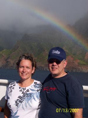 Picture of a couple and the Maui coastline with a rainbow.
