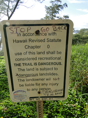 Picture of the warning sign on the trail to the Red Sand Beach near Hana on the island of Maui, Hawaii.