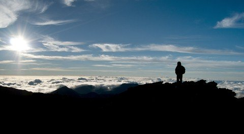 Person watching sunrise on Haleakala.