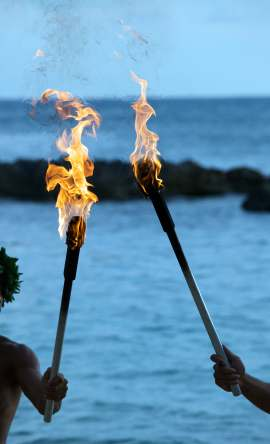 maui luau torches lighting beach at sunset